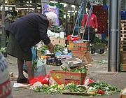 Una donna recupera verdure tra gli scarti di un mercato rionale (Ansa)
