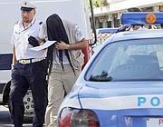 Il conducente, col volto coperto, portato via dalla polizia (foto Mario Proto)