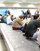 Passeggeri in attesa di bagagli nello scalo di Fiumicino (Ansa)