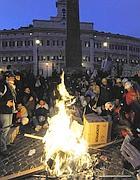 Gli operai di notte a Montecitorio si scaldano con il fuoco (Reuters)