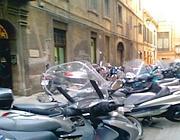 Moto parcheggiate in una stradina del centro