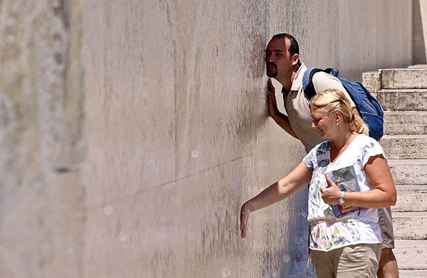Caldo record in città - Caldo record con punte previste di 38 gradi centigradi giovedì a Roma, ma già mercoledì la colonnina di mercurio è salita oltre i 30 gradi in centro e molti turisti hanno cercato refrigerio presso le fontane della capitale: nella foto  Jpeg, due visitatori si rifrescano con l'acqua della fontana progettata da Richard Meier presso la nuova teca dell'Ara Pacis. Giovedì le massime in città dovrebbero toccare i 35 gradi ma in alcune zone l'effetto riscaldamento di cemento e asfalto portrà le temperature percepite intorno ai 40