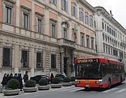 Un bus transita di fronte Palazzo Grazioli (Ansa)