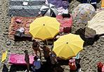 La spiaggia è un quadro - Geometrie casuali eppure incredibilmente armoniose, colori sgargianti e toni pastello su fondo grigio: ombrelloni, teli da bagno e lettini compongono in questa foto un'immagine che sembra un quadro. La fotografia è stata scattata a Ostia durante i controlli aerei di Ferragosto dall'elicottero della Polizia di Stato  (foto Ansa/Di Meo)
