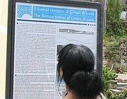 Turista legge il cartello che racconta le origini del tunnel romano (foto Proto)