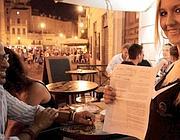 Una cameriera mostra l'ordinanza di Alemanno che d'estate vieta la vendita di alcolici a tarda sera (foto Jpeg)