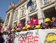Studenti e precari con i caschi gialli davanti al ministero (foto Ansa)