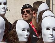 Le maschere bianche degli studenti guardate a vista dalla polizia (Ansa)