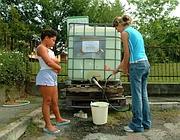 Distribuzione di acqua potabile in un comune lombardo (Newpress)