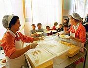Distribuzione dei pasti in  una mensa scolastica (Fotogramma)
