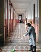Una bidella intenta a pulire una scuola (Fotogramma)