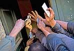 L'attesa - Via Quattro Novembre 107, Chiesa Evangelica Valdese: molti extracomunitari,  aspettando di ottenere  dei vestiti, mostrano i propri documenti a una donna (foto Mario Proto)
