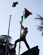 Un manifestante a Roma  sostituisce la bandiera issata in via Nomentana(foto Eidon)