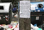 Cassonetti inutili - La spazzatura davanti ai cassonetti della raccolta differenziata nel municipio XV (Arvalia - Portuense). Nella foto si vede un cartello che implora di non buttare a terra i rifiuti e indica le modalità della raccolta stabilite dall'Ama per conto del Comune di Roma. Ma qualcosa non funziona (foto Eidon)