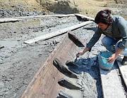 Un'archeologa al lavoro, pulisce lo scafo (Faraglia)