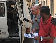 Un ambulante col bracciale accompagnato dai vigili urbani di Roma (Jpeg)