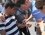 Vigili in borghese applicano il bracciale a un immigrato (foto Jpeg)