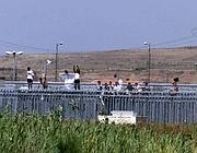 Una protesta di immigrati sui tetti del centro (Ansa)