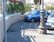 Un'auto parcheggiata sulla ciclabile del Circo Massimo, tracciata con la vernice sul marciapiedi