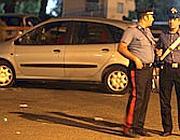 I carabinieri con alle spalle l'auto colpita (Ansa)