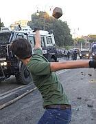 Un ragazzo lancia un sampietrino contro i blindati (foto Salmoirago)