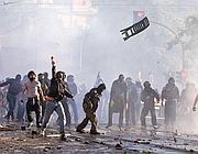 Un gruppo di teppisti durante gli scontri in San Giovanni: lanciano sassi e perfino una sedia (Ansa)
