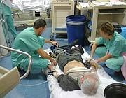 Medici curano un malato sul pavimento al S. Camillo (Ansa)