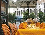 I tavolini vista Colosseo dell'Hostaria al Gladiatore su via dei Santi Quattro