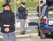 L'auto dei rapinati e, sullo sfondo, il bandito morto nella sparatoria (Proto)