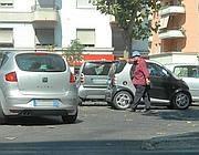 Un abusivo fa segno a un automobilista di parcheggiare in doppia fila (foto Proto)