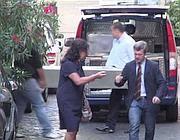 La moglie di De Pedis con il suo legale, sullo sfondo la bara dell'ex boss viene caricata su un furgone (Proto)