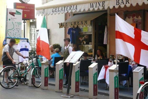 """Bike-sharing e caffé - """"La postazione di bike-sharing all'inizio di Via del Corso (lato Piazza del Popolo) è ormai usata dall'esercizio commerciale lì di fronte: menu in mezzo alle colonnine, cartelloni pubblicitari che coprono il totem, magliette, palloni,  bandiere. L'Assessore Visconti, delegato allo sviluppo della mobilità ciclistica, aveva annunciato mesi addietro un nuovo bike-sharing; di nuovo c'è solo il fallimento di questo e del bando per il nuovo che era stato predisposto dall'amministrazione capitolina. La situazione è ben rappresentata dalle foto in allegato e visto lo sfascio in cui versa quasi verrebbe da giustificarne l'uso che ne fa l'esercizio commerciale"""" Foto e segnalazione di Fausto Bonafaccia (Fondatore e Presidente BiciRoma - Associazione Due Ruote d'Italia onlus)"""