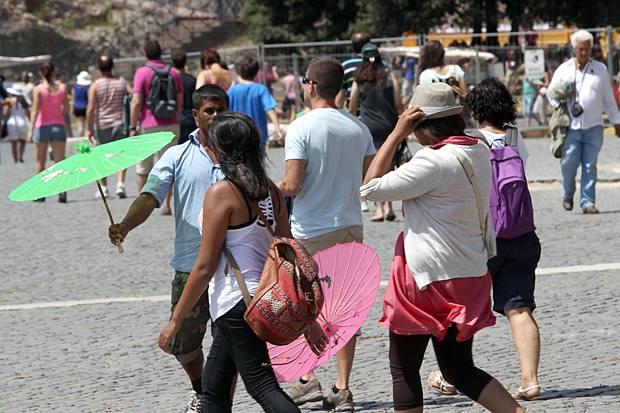 Ombrellini abusivi - Domenica di solleone. Quasi 40 gradi percepiti: i turisti si difendono come possono. E intorno al Colosseo è il trionfo delle bancarelle abusive: gli ambulanti non autorizzati vendono di tutto, ma il souvenir più richiesto è un colorato parasole. Un ombrellino cinese naturalmente. All'Anfiteatro Flavio è tornato il suk  (foto Jpeg)