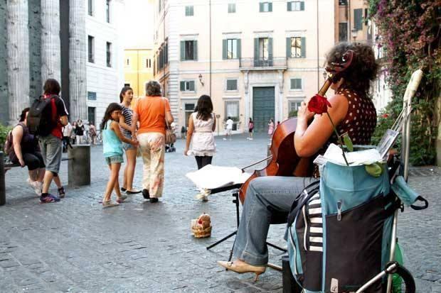 Note al Pantheon - Nel caldo ancora soffocante del pomeriggio di luglio, solo una bambina sembra accorgersi della musica delicata di un violoncello, suonato in piazza di Pietra da una giovane strumentista. Per i grandi invece la musica si perde nel caos di una città che sembra incapace di fermarsi anche solo un istante per ascoltare chi sussurra (foto e testo del lettore Paolo Cerino)