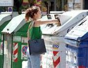 Una ragazza deposita la carta nel bidone della differenziata (Jpeg)