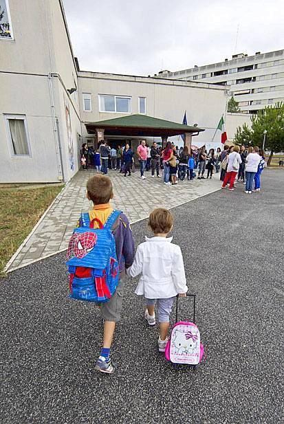 Tutti sui banchi - Sono tornati tutti sui banchi di scuola gli studenti romani (oggi era la volta delle superiori, medie e elementari avevano già iniziato nei giorni scorsi). Nella foto Ansa, due fratellini raggiungono la scuola