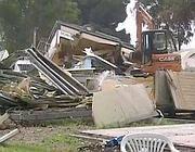 Una delle ruspe abbatte container e roulotte