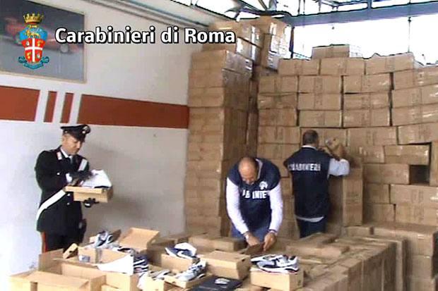 Un «muro» di Nike false - Più di diecimila paia di scarpe con marchi contraffatti, contenute in 866 scatoloni, pronte per essere messe sul mercato: è il maxi-sequestro effettuato dai Carabinieri della Compagnia di Tivoli a conclusione di una intensa attività investigativa. Sei le persone denunciate a piede libero tra cui 3 cinesi, 2 marocchini ed un italiano, accusati di introduzione e vendita di prodotti con segni falsi, frode nell'esercizio del commercio e ricettazione.  L`ingente quantità di calzature tarocche, fedeli riproduzioni di modelli «Nike» perlopiù delle costose «Air Max», è stata intercettata dai militari dell`Arma in un capannone di Tor Vergata, periferia sud della Capitale. Al momento del blitz, i Carabinieri hanno sorpreso cinesi e marocchini mentre caricavano i numerosi colli, disposti con ordine certosino, su di un camion e un furgone, anch'essi sequestrati (foto Proto)