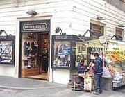 Un negozio di vestiti e un chiosco di frutta aperti  a Natale all'angolo tra via del Corso e via della Croce