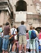 Turisti intorno ad una guida al Colosseo (Eidon)