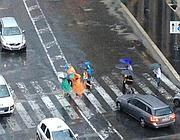 Turisti con colorati mantelli di plastica sotto la pioggia lunedì