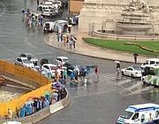 Turisti con mantelli e ombrelli a piazza Venezia